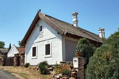 Hungarian peasant version of Classical old stone cottage in the Kali Basin features thatched roof, whitewashed walls, and plaster carvings Stone Cottages, Thatched Roof, Interesting Buildings, Old Stone, Old Buildings, Basin, Travel Photography, Sweet Home, Architecture
