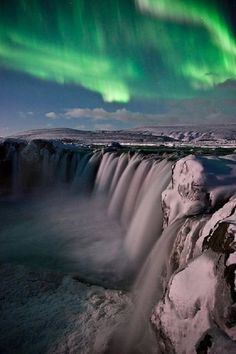 Aurora Borealis over Goðafoss waterfalls in Iceland