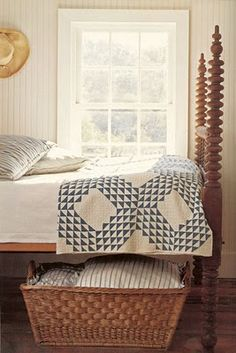 Love the bed and exquisite quilt -- French basket under the bed for additional linen storage!