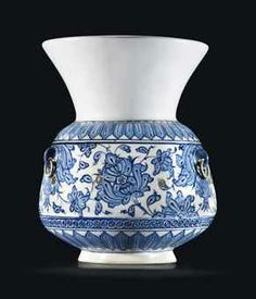 """A rare early Iznik Mosque Lamp (Kandil) Ottoman Turkey, Circa 1512 - Of typical form, with cylindrical body tapering before wide flaring mouth, the white body painted in two shades of blue with a band of elegant fleshy palmettes on a meandering scroll, a band of stapwork roundels containing stellar motifs below, wider bands of hexagonal lozenges before the foot & mouth, the body with three loops for hanging, Overall 8½""""; body 5"""" high [Auction estimate $166,100 - $249,150]"""