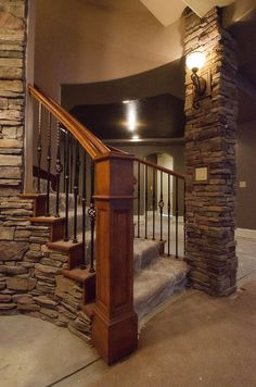 stacked stone, newels, iron balusters and the torch style sconce lighting is a whimsical, dungeony touch.