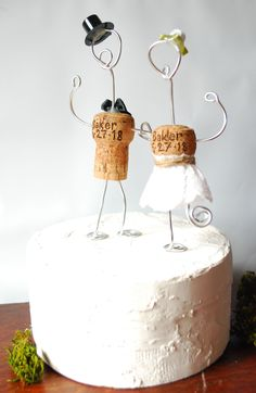 Rustic Champagne Cork Wedding Cake Toppers. These can be PERSONALIZED WITH YOUR WEDDING DATE! Handmade in the PNW with satin bows, country lace, & topped with a top hat! Beautiful and elegant addition for your wedding decor. These toppers also can be used as tree ornaments for a lasting keepsake. #countryweddingcakes #weddingdecoration
