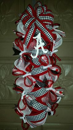 This is an Alabama Crimson Tide deco mesh door hanger made from red and white deco mesh and houndstooth and Alabama ribbon accented with a small 4 white wooden script A letter. *Can do ANY team, just ask. Alabama Football Wreath, Alabama Wreaths, Mesh Ribbon Wreaths, Deco Mesh Ribbon, Wreath Forms, Alabama Crimson Tide, 4th Of July Wreath, Diy And Crafts, Roll Tide