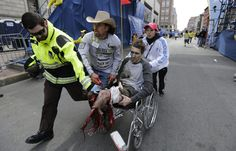 Medical workers runs an injured man past the finish line the 2013 Boston Marathon following an explosion in Boston, Monday, April 15, 2013. Two explosions shattered the euphoria of the Boston Marathon finish line on Monday, sending authorities out on the course to carry off the injured while the stragglers were rerouted away from the smoking site of the blasts. (Charles Krupa / AP)