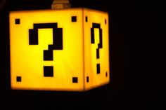 Its-a-me! Mario lamp!  Very bright lamp has the question mark on all 4 sides, and an open bottom to make it perfect for hanging over a table or couch. Extra long lamp cord is capable of hanging the entire unit safely, and comes with two hooks for easy installation. Takes any standard light bulbs, not recommended to use a bulb over 75 watts. Measures 6 on all sides. Features: - Beautiful 4 sided design - Energy efficient bulb included - Long 15 cord capable of hanging the lamp - Open bottom…