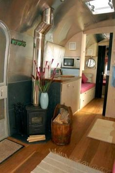 Airstream living. Wood floors and a wood stove. In my dreams!