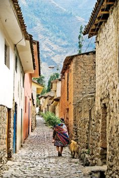 Travel Inspiration for Peru - A local Peruvian woman walks down a road in the Ollantaytambo Village.