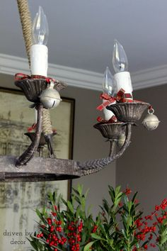 Jingle bells tied around candles of chandelier with plaid ribbon for Christmas!