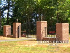 Wrought iron driveway gate and fence combined with brick pillars and a knee wall for a beautiful, but clean entryway