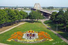 Bloemenwapen van Nijmegen in het Hunnerpark, met de Waalbrug op de achtergrond.  gelderland, nederland,