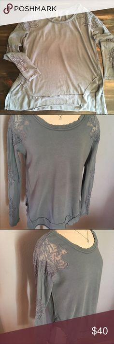 Free People L/S Top Size Medium. This is a top by Free People in size medium. It has the prettiest lace sleeved detailing going from shoulder and down to the cuff of each sleeve. It also has large slits on the bottom of both sides to give you that more flattering fit. This top is super cute and in good condition. Free People Tops