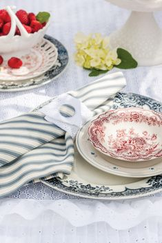 Since one cannot pluck a cloud from the sky to dress the table, a pretty cloth made of snow-white eyelet makes a suitable stand in. With a simple snap or a touch of Velcro, a snippet of fabric with corresponding design encloses a ticking-stripe napkin. Ticking Fabric, Ticking Stripe, Shabby Chic Homes, Shabby Chic Decor, Victoria Magazine, Napkin, Tablescapes, Cloud, Snow White