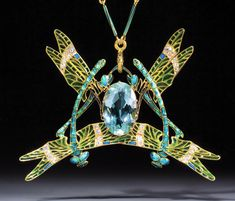 Pendant | René Lalique. 'Dragonfly'  Gold, diamond and enamel.  This signed piece made c1903 depicts four dragonflies with green-blue enamelled legs and wings with a large oval acquamarine in its centre. It was originally purchased directly from Lalique by the glassmaker Leon Appert, the brother-in-law of the great French painter Georges Seurat.