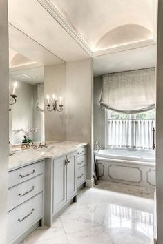 Elegant French bathroom boasts gray painted barrel ceiling over nook filled with gray extra-long ...