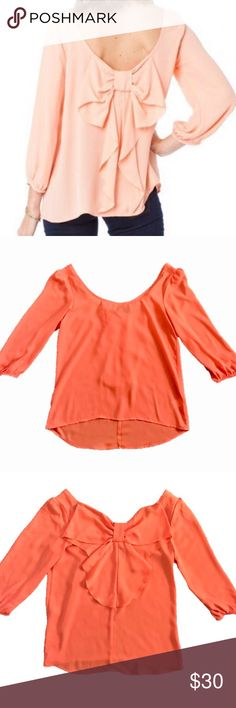 NWT Francesca's Orange Bow Back Blouse Size Small Adorable NWT Francesca's blouse by Blue Rain. This blouse is new with tags and in perfect condition, never worn. Light orange/peach (model is wearing a pink color). Large bow on back. 3/4 sleeves. 100% Polyester. Size Small. Francesca's Collections Tops Blouses