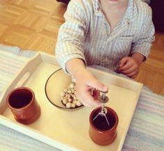 une pince à sucre, deux vieux pots de yaourt en gré, un bol rempli de perles en bois