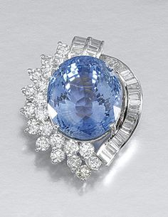 SAPPHIRE AND DIAMOND PENDANT AND BROOCH. Each set to the centre with an oval and shield-shaped sapphire respectively, to an abstract surround set with heart-shaped, brilliant-cut and baguette diamonds, chain length approximately 480mm, part illustrated.