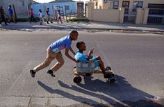 In this Monday, July 2015 photo, a child pushes a friend in a home-made go-kart in the Khayelitsha township near Cape Town, South Africa. The vehicle was built with recycled wood, plastic containers and old nails.