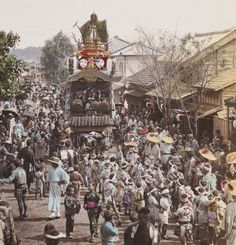 Festival in Yokohama, featuring a large float.  Hand-colored photo, circa 1890, Japan.    Photographer unknown