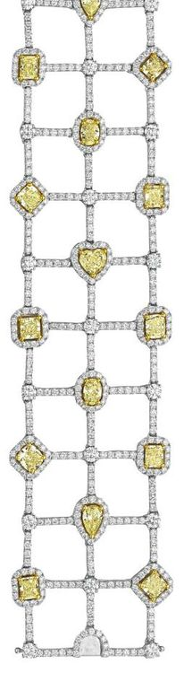 A Diamond and Yellow Diamond Bracelet. Of flexible design, the wide openwork band composed of three rows of vari-cut yellow diamonds, within a circular-cut diamond surround, interspaced with circular-cut diamond connector links, mounted in 18K white gold, length 7 1/2 inches. Philips de Pury.