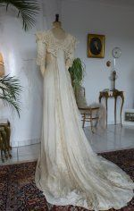Exquisite Belle Epoque Wedding Gown, ca. 1909..Fabulously and exquisite Belle Epoque gown from around 1909. It is made of silk and has so such lovely detailing all throughout! The scoop neck is adorned with lace and beading around the collar that has a piece cascading down from the left side. There is beading all down the left side and across the lower waist line that leads to two panels in the back with detailed beading