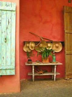 The classic tones of Mexico are showcased on this rust painted wall with a timber barn-style doors contrasting in a wash-out celadon. The interesting decorative touch is the playful row of straw hats arranged above a small outdoor console. Mexican Interior Design, Mexican Designs, Mexican Hacienda, Hacienda Style, Mexican Colors, Mexican Style, Wall Colors, House Colors, Colours