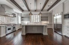 White and gray kitchen features a tray ceiling lined with wood beams and a pair of Currey and Company Syllabus Pendants illuminating a gray center island fitted gray and white marble countertop framing a corner prep sink situated across from gray open shelving flanking window.