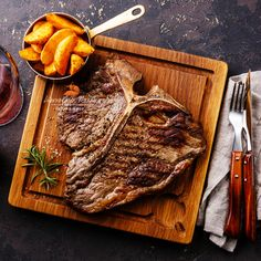 ти-бон стейк - Medium rare Grilled T-Bone Steak with potato wedges and wine on serving board block on dark background