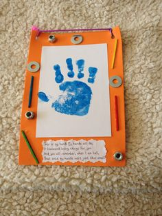 Father's Day toddler craft made with a foam frame, painted handprint on paper, and glued on bolts/nuts/screws