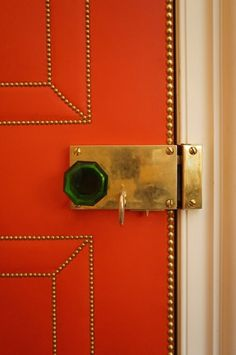 Orange Lacquer and Brass Nailhead Trim, with a gorgeous green glass handle and brass lockset, make a fun play on upholstered doors Knobs And Knockers, Door Knobs, Door Handles, Door Design, House Design, Do It Yourself Home, Nailhead Trim, Messing, Doorway