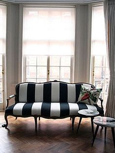 striped sofa and botanical throw pillow take center stage in this understated, elegant room.