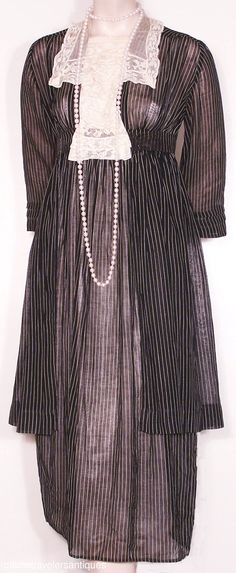 """1914 ... Day Dress ... sheer black and white striped lawn dress with a separate overskirt, a ruffled Valenciennes lace jabot insert and collar, and a front hook and eye closure. ... 14"""" from shoulder to shoulder, a 34"""" chest, 27"""" high waist,and 46"""" from shoulder to front hem. ... from Time Travelers on eBay ... photo 1"""