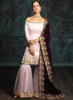 Light Pink Gharara Suit with Deep Plum Shawl features a dhupioni silk kameez with santoon inner, net bottom and santoon inner alongside a velvet shawl dupatta. Embroidery work is completed with zari, stone and sequins work embellishments.