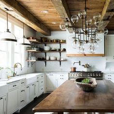 Farmhouse kitchen with white cabinets exposed beams and wood ceiling, a large wood island, and a contemporary statement chandelier.