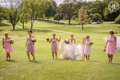 Bride walking with her bridesmaids across country club golf course