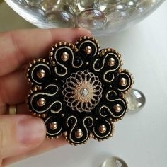 Black and gold soutache brooch with gold pearls, gold and black beads and cabochon in a flower shape