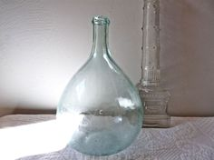It is superb and graceful, it looks like a soap bubble!  I love finding this kind of object in the flea markets I visit all during the spring and summer here in my part of France...but like so many things, they are becoming harder to find.  This beautiful bottle was blown with the mouth, it dates from the late 19th century.  Look closely at the neck Demijohn, we see that the necklace was made and laid by hand, it looks like a piece of chewing gum.  this demijohn contains 3 liters.  It is a…
