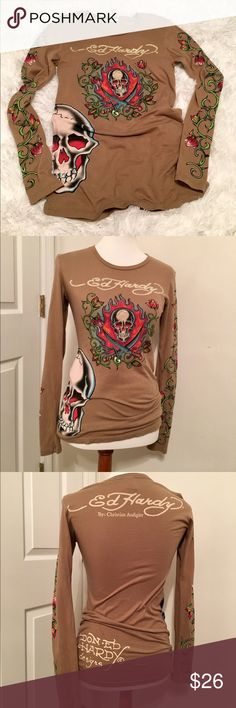 Ed hardy t-shirt Ed Hardy long sleeved t-shirt. The graphic on the front is embellished with multi-colored rhinestones and sleeves have a floral vine pattern. Longer style. 100% cotton. This is a size medium, but it's a more snug fit instead of baggy t-shirt fit. Would also work for a small size. **Smoke free home** Ed Hardy Tops Tees - Long Sleeve