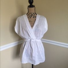 White Torrid Blouse This is a beautiful white top from Torrid size 0x/L. It has an elastic waistband, buttoned sleeves, & vertical line print. It is lightweight & perfect for spring/summer weather! Semi sheer, 100% cotton. Excellent condition. torrid Tops