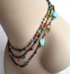 A shimmering mix of teal, greens, lavender, amber, and copper colored glass beads are crocheted on chocolate brown cotton thread. It can be worn as a