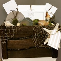 A nautical basket filled with seafoam colors, including monogrammed, starfish notecards, acrylic coasters, and personalized anchor notepads.