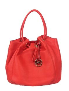 Michael Kors Ring Tote Circular rolled handles loop through goldtone grommets at the top of a supple leather tote with a lush tassel and a dangling cutout logo medallion at one side.