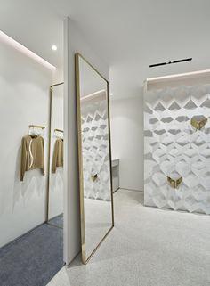 Стена отделана белоснежными пластинами с золотыми вставками