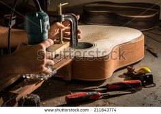 Luthier cutting a channel to place the truss rod in the guitar neck - stock photo