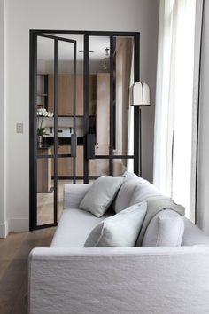 grey metal framed doors, blonde wood kitchen and chalk white linen sofa