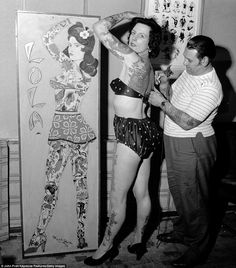 pam nash being tattooed by les skuse. standing next to a board illustration of what her completed work will look like.