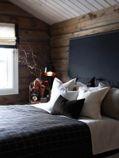 Rustic- wood panelled walls, black headboard, cosy bedding, masculine design