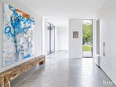 Form meets function in the gallery/ mudroom. Created to connect the main house with the garage, the room boasts ample wall space to display art and, on the more practical side, a bench fashioned from the salvaged living room fireplace mantel serves as seating for removing shoes and boots. The dark gray Italian limestone floors are from Paul's Marble Depot.