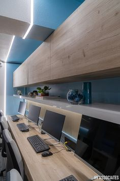 The blue office interior is lightened up with some plantation and a wooden staircase. Office Cabin Design, Small Office Design, Corporate Office Design, Office Furniture Design, Corporate Interiors, Office Interiors, Commercial Design, Commercial Interiors, Blue Office