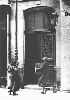 A Jewish women carries her radio into a police station after a German order (August 8, 1941) demanded the confiscation of all radios owned by Jews. Paris, France, 1941.  — Bibliotheque Historique de la Ville de Paris